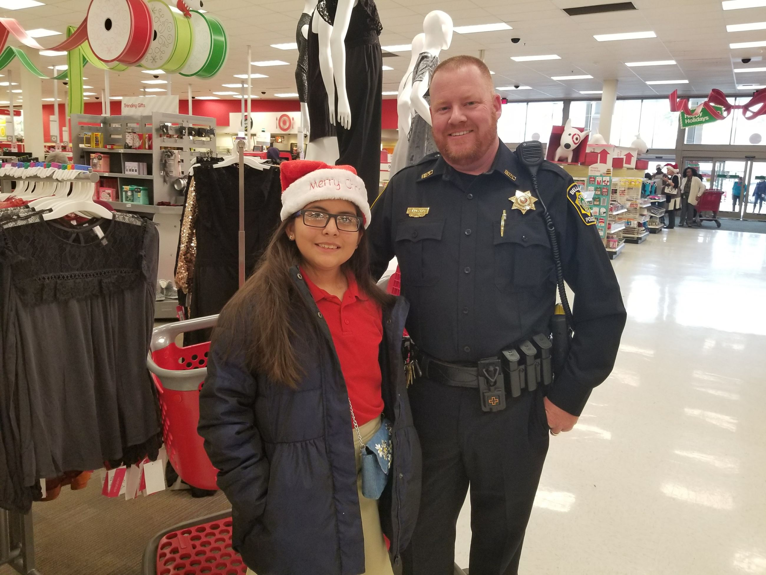 Officer and girl smile together at Shop with a Cop event